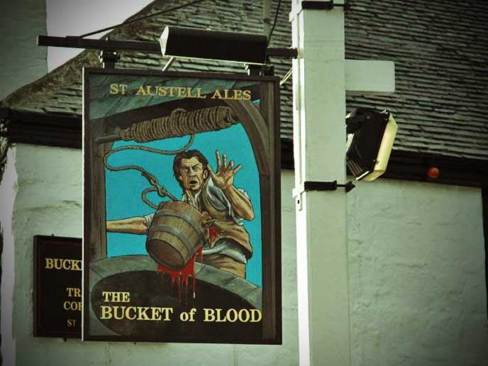 The sign for the Bucket of Blood shoign a startled landlord by a bucket film with blood..