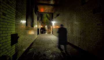 The shadow of a ghost walk guide in an alley in London.